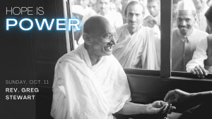 Black and white photo of Mahatma Gandhi on a train with people looking in