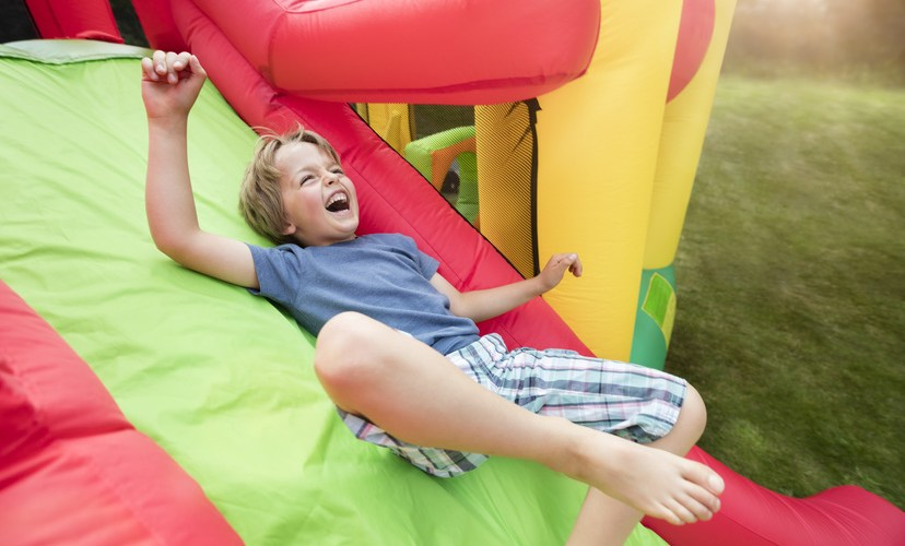 Bild lachender Junge auf Mini-Hüpfburg
