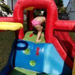 Kind klettert auf Hüpfburg mit Wasserrutsche
