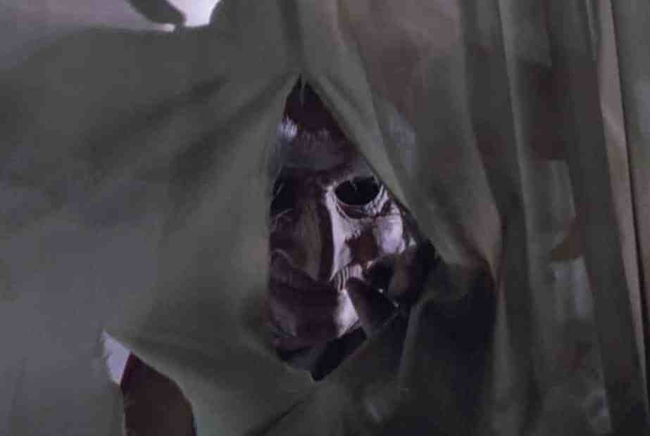 Jester's face poking through a torn sheet
