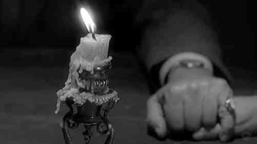 A hand holding another and a dripping candle nearby