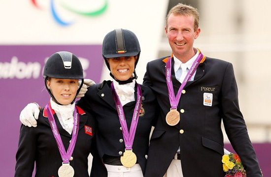Michele George of Belgium celebrates winning gold with Sophie Wells of Great Britain, left, and Frank Hosmar of The Netherlands, for the Individual Championship Test - Grade IV at the London 2012 Paralympic Games at Greenwich Park.
