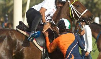 A runner switches to horseback during a transition during the Dubai Desert Marathon.