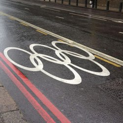Olympic rings marked on a street in London, indicating that the lane was reserved for the use of Olympic athletes and staff. By carlbob (Flickr: Games Lane) [CC BY 2.0 (http://creativecommons.org/licenses/by/2.0)], via Wikimedia Commons