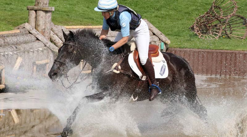 Jonelle Price and Classic Moet power through a water obstacle to take the lead at the Badminton Horse Trials in Britain.