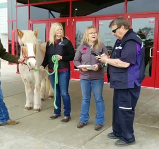 Blaze and HopeWell ranch director Jodi Stuber receive the FedEx delivery of Unbridled at the Celebration Cinema in Michigan.