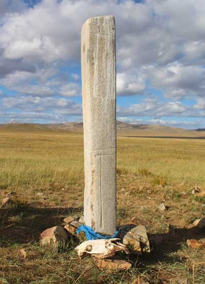 A horse skull placed next to a deer stone in central Mongolia. Horse skulls are revered by modern herders, as are deer stones – this one has been decorated with a ceremonial blue prayer scarf. Photo: William Taylor