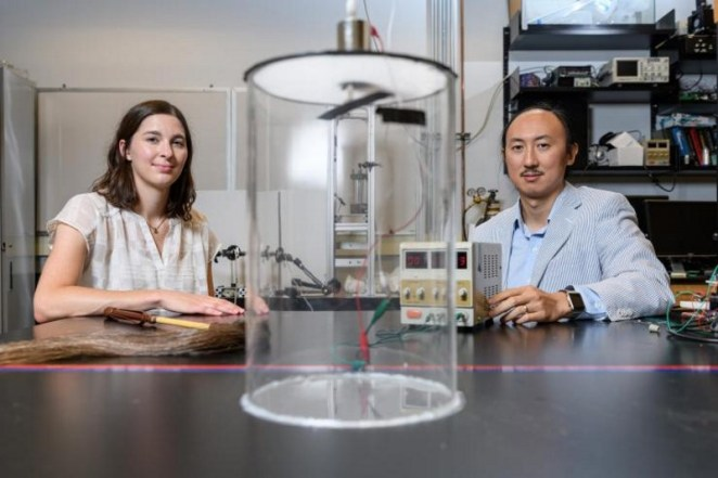 Marguerite Matherne, a mechanical engineering Ph.D. student, and Professor David Hu, pose with the mammal tail simulator used to study the airflow needed to keep mosquitoes from landing. (Credit: Rob Felt, Georgia Tech)
