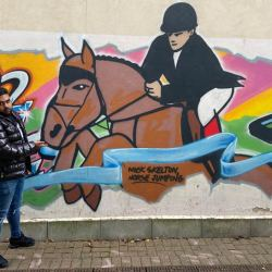Reece McCook with a mural of showjumper Nick Skelton, one of the riders supporting the new #IamPartoftheChange campaign. © Kim White