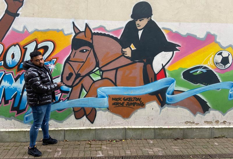 Reece McCook with a mural of showjumper Nick Skelton, one of the riders supporting the new #IamPartoftheChange campaign.