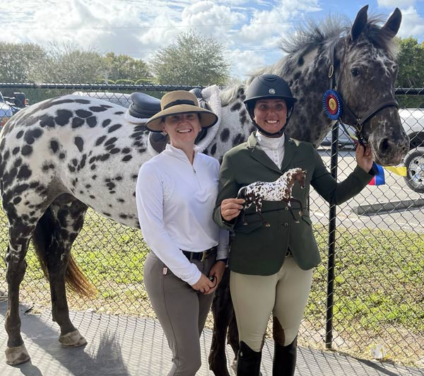 Dani with owner/rider Laura Reece and trainer Ashley Glica, with Dani's 2021 BreyerFest Celebration Horse model.