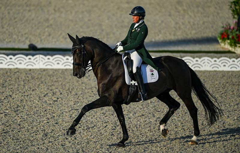 Heike Holstein and Sambuca on the second day of the dressage qualifying rounds during the 2020 Tokyo Summer Olympic Games in Tokyo, Japan. Irish team members are wearing a yellow ribbon in commemoration of Tiggy Hancock.