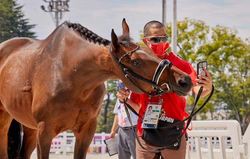 Japan's Grade IV rider Katsuji Takashima and Huzette pose for a selfie after the horse inspection at the Tokyo 2020 Paralympic Games.