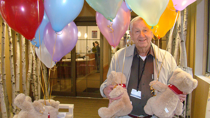 Volunteer With Balloons And Teddy Bears