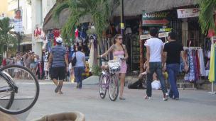 Gente en playa del Carmen transportandose en bicicleta