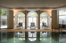 Poolchairs overlooking an indoor hotel swimming pool