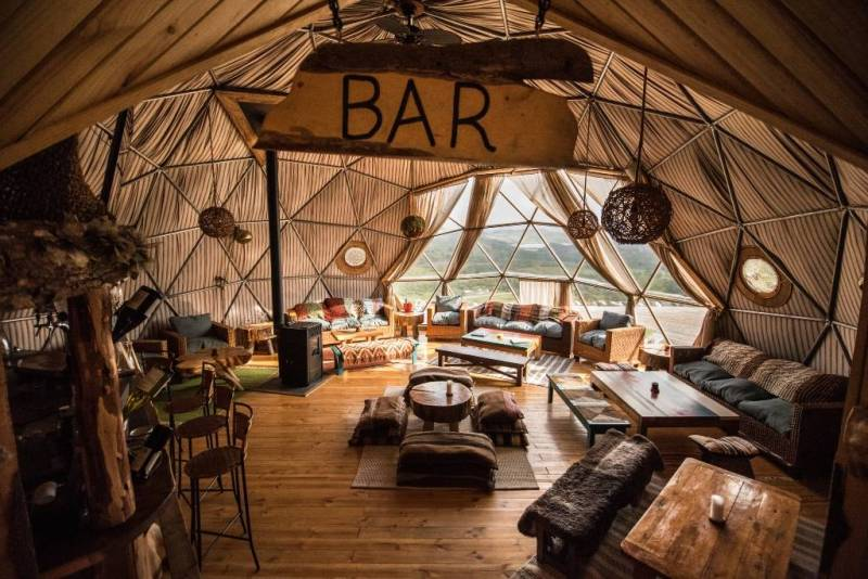 """Expansive interior of dome with large """"Bar"""" sign and various types of lounge seating."""