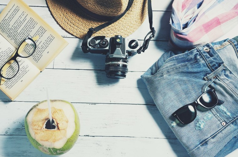 Jeans, shades, a sun hat, camera, book, glasses, and even an apple incense holder—the quintessential travel items.