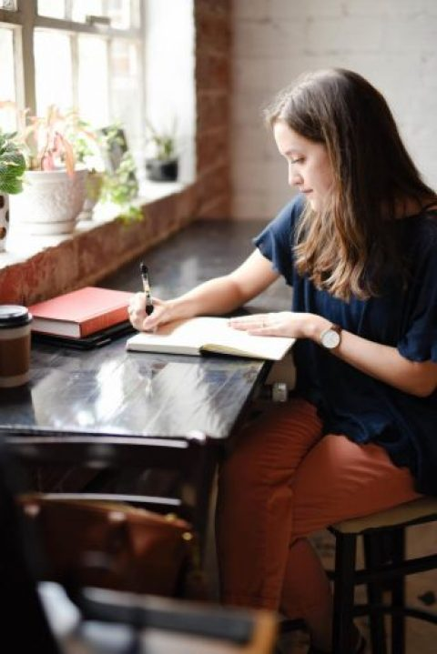 Woman practices gratitude by writing in her journal.