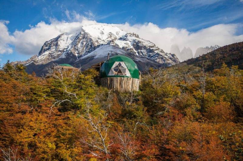 Green dome rises above trees with mountain backdrop.