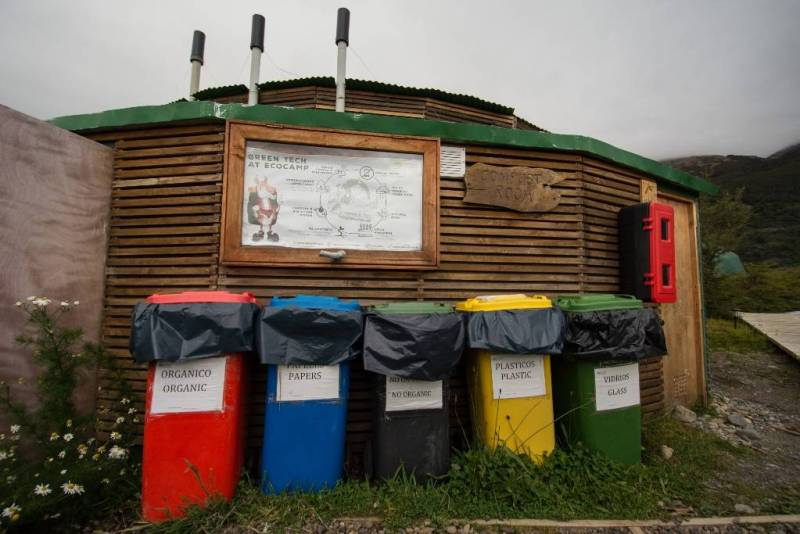 Red, blue, black, yellow and green recycling and compost cans at EcoCamp Patagonia.