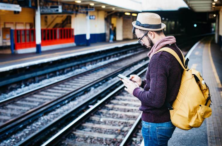 Man wearing fedora and backpack waiting for train while looking at phone.