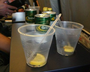 A couple empty plastic cups with lemons and tonic water cans on an airplane tray table.