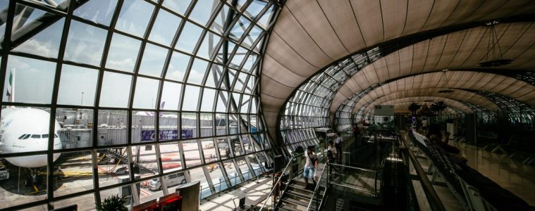 Large square glass panes provide a view of the tarmac in spacious airport terminal.