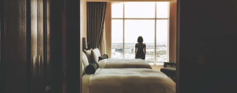 Woman looks out a large hotel window in beautiful day hotel room.
