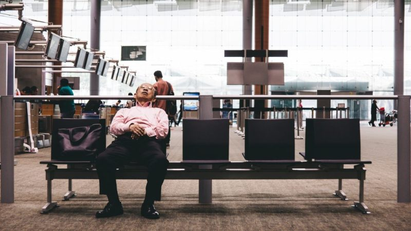 Man leans back and takes a quick siesta in empty airport terminal.