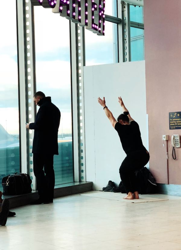 Man stretches arms high in yoga pose in a corner of the airport before a long flight.