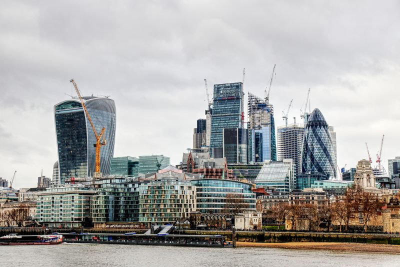 A backdrop from the Thames River of London's modern architecture juxtaposed by smaller, historical buildings.