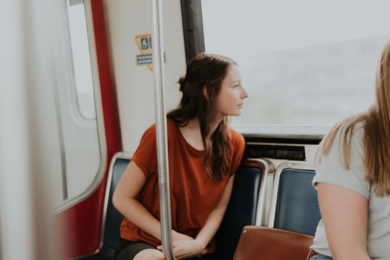 Woman excitedly looks out window on public transportation while exploring a new city.