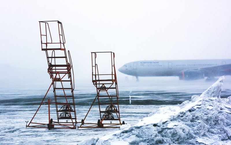 Air stairs, airplane and snowy tarmac with the grey abyss all around.