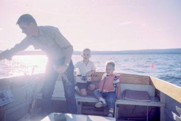 Two sons fishing with their dad to celebrate Father's Day on a bright sunny day in the U.S.
