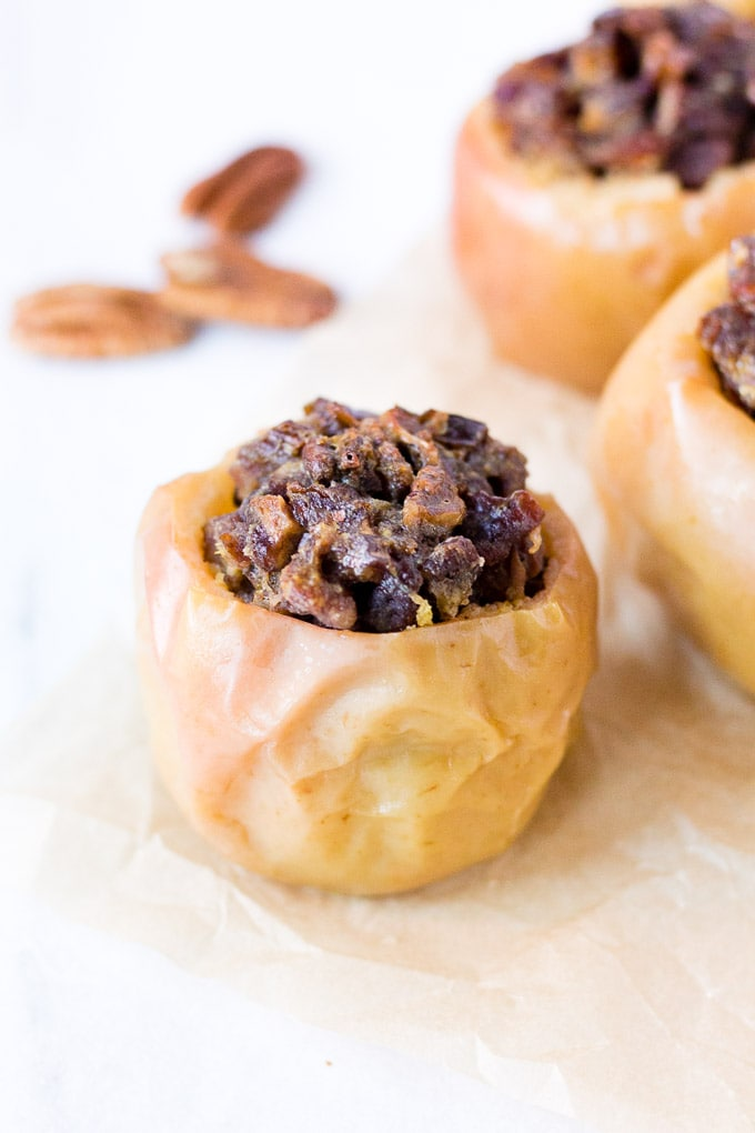 a baked apple with ginger, dates, and pecans in the filling on a piece of parchment paper. three pecans are in the background to the left and two other apples to the right.