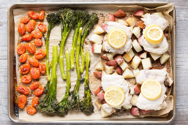 roasted tomatoes and broccolini with cut up potatoes and chicken thighs with lemon slices on a sheet pan