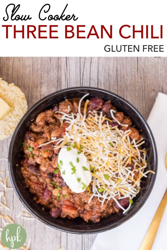 This Gluten Free Slow Cooker Three Bean Chili is an easy recipe for weeknight dinner. Cook up the ground beef, dump everything into the slow cooker, then let it cook until dinner time. Great for a crowd, or just a hungry family. Serve with cheese and sour cream, plus some cornbread on the side! #chili #glutenfree #crockpot #slowcooker #comfortfoods