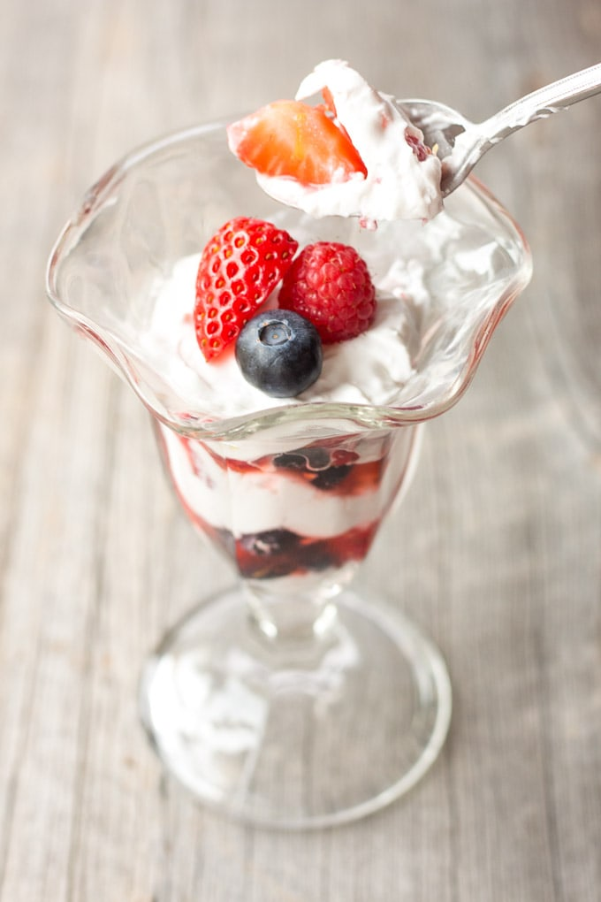 Spoon scooping a bite of Simple Summer Berry Paleo Parfait out of a parfait glass