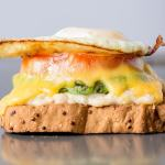 eye level shot of a gluten free tuna melt with avocado, tomato, and fried egg on a sheet pan