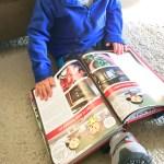 little boy flipping through a cookbook on the floor