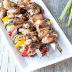 gluten free teriyaki chicken kabobs on white platter with scallions and garlic to the side