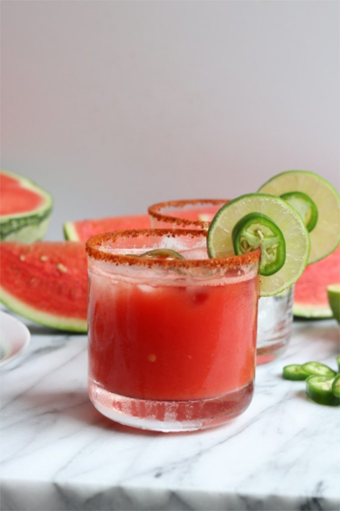 watermelon jalapeno margaritas in short glasses rimmed with salt and a lime and jalapeno garnish