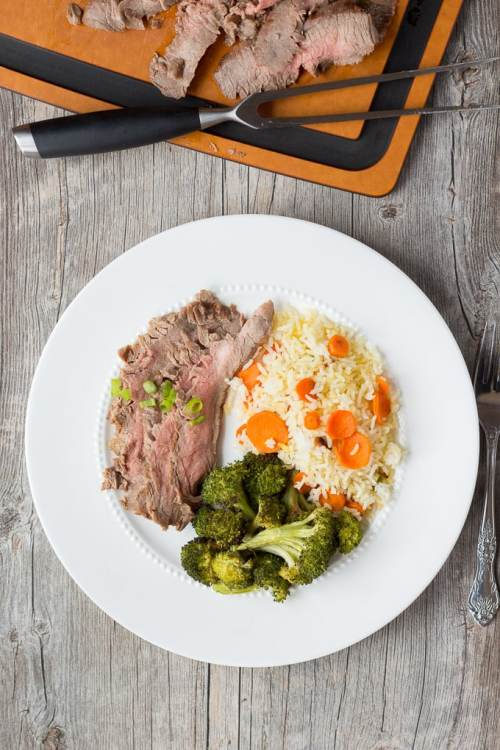 white plate with flank steak, roasted broccoli, and white rice with carrots. Above it is a brown and black cutting board with a butcher fork and slices of flank steak