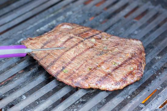 checking the temp on gluten free flank steak on the grill