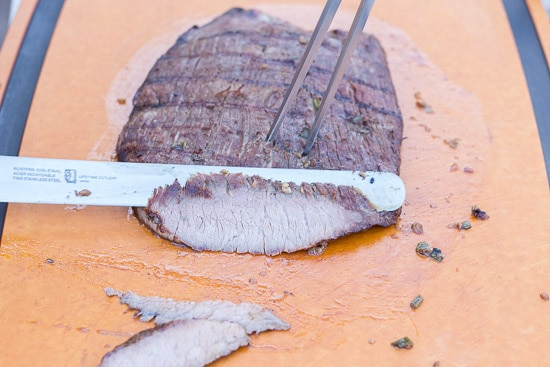 cutting into gluten free flank steak on a large brown cutting board