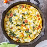 breakfast frittata in a cast iron skillet with a green and white towel, several cherry tomatoes, and a white plate