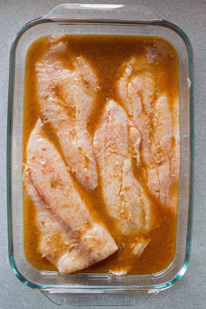fish in glass dish marinating in easy fish taco marinade