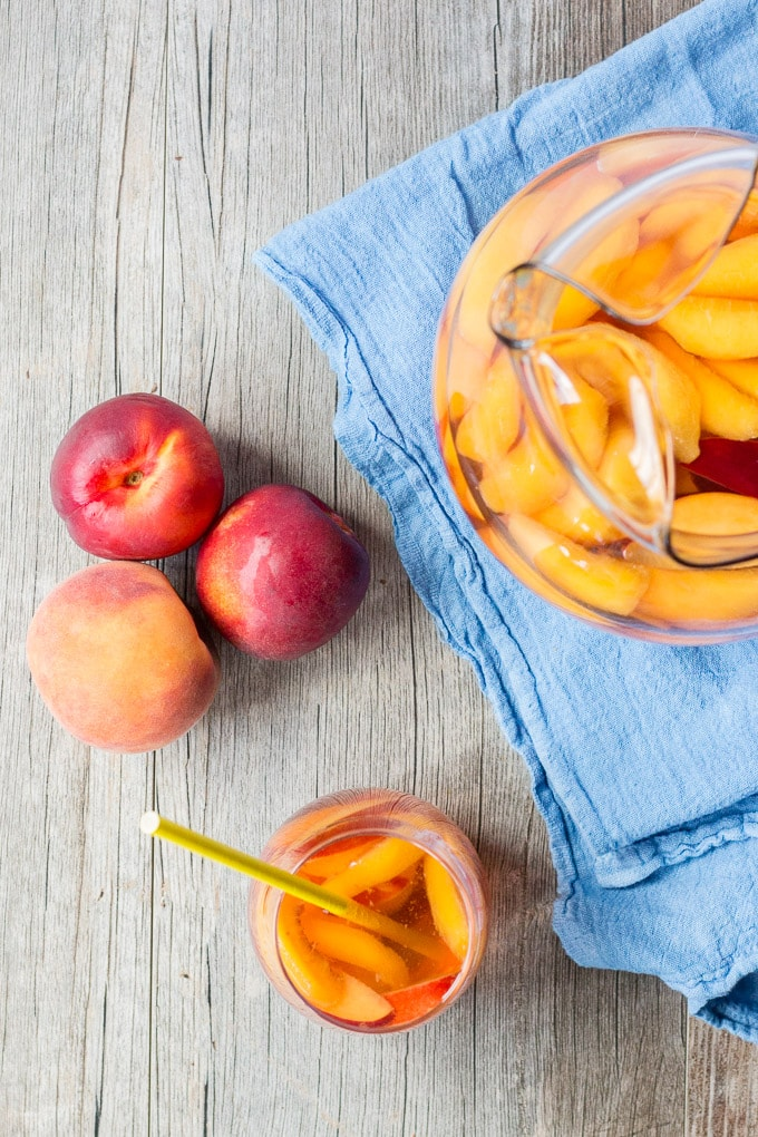 overhead shot of 1 peach with 2 nectarines, a glass pitcher on a blue towel filled with sangria, and a stemless wine glass filled with sangria and a yellow straw.