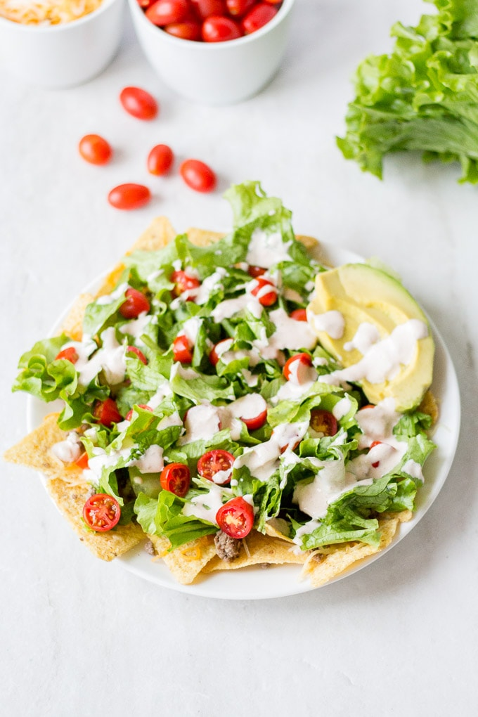 easy nacho salad on a white plate with small white bowl in the back left containing shredded cheese and cherry tomatoes. green leaf lettuce is in the upper right corner and five cherry tomatoes are on the ground.